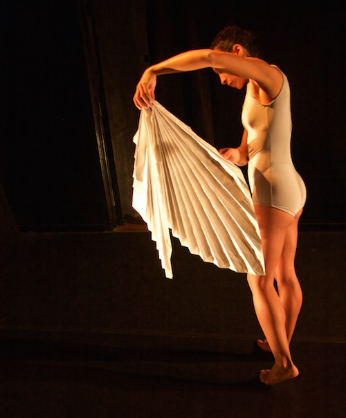 Dance Marielis Garcia clad in a light blue leotard holds out an intricately folded white paper sculpture that billows out from the bottom