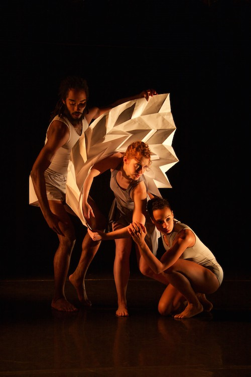 The trio of dancers huddle around a square-shaped accordion looking paper