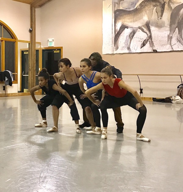 Members of BalletNext in leotard and rehearsal clothes squat in a second position near one another