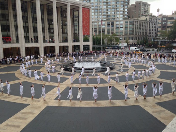 Some dancers sit crosslegged while other lean against the plaza's center fountain