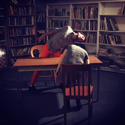 Two dancers shake their head around a library table.