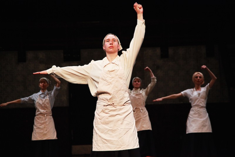 Performers in white aprons and hankerchiefs on their heads with one arm above their heads and another outstretched