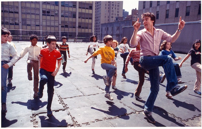 Jacques leads a group of kids on the roof of their school. Their knees are hiked into the air.