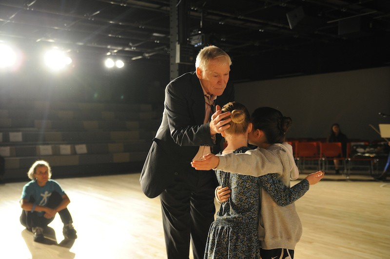 Two young girls embrace on the NDI stage, Jacques and another teacher coach them