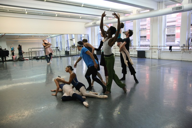 The cast of New Notes during a studio rehearsal. They pose in a tableau with some dancers sitting on the floor while others stand. A couple dancing is in the background. The dancers wear practice clothes.