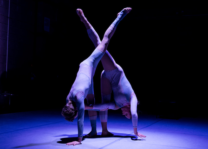 The two dancers both touch the ground with their hands while their left legs are raised to the ceiling and cross at the knee