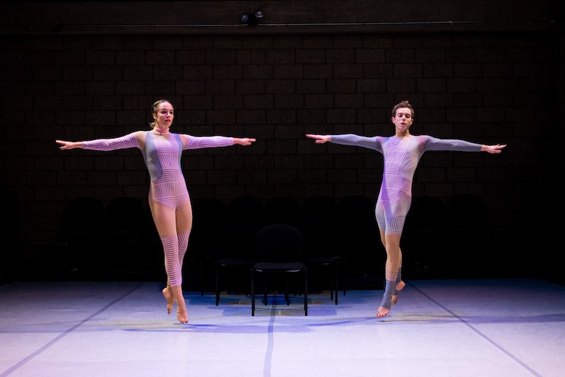 The two dancers both jump into the air towards the center of the stage in a symmetrical configuration with deadpan stares