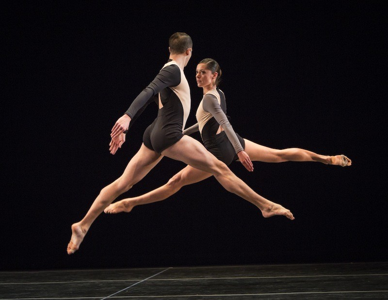 Joshua Tuason and Melissa Toogood in Locomotor.  Both dancers look at one another as they leap in the air, splitting both legs perpendicular to the floor.