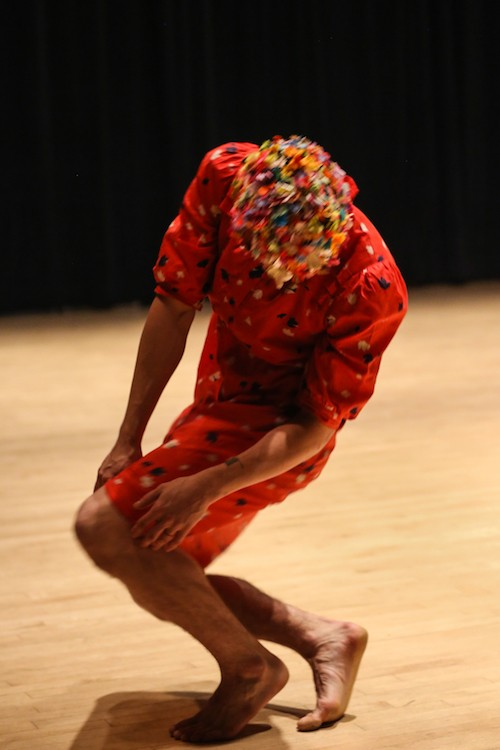 Brian Strimpel in a red house dress and mask. He squats down as he balances on the balls of his feet.