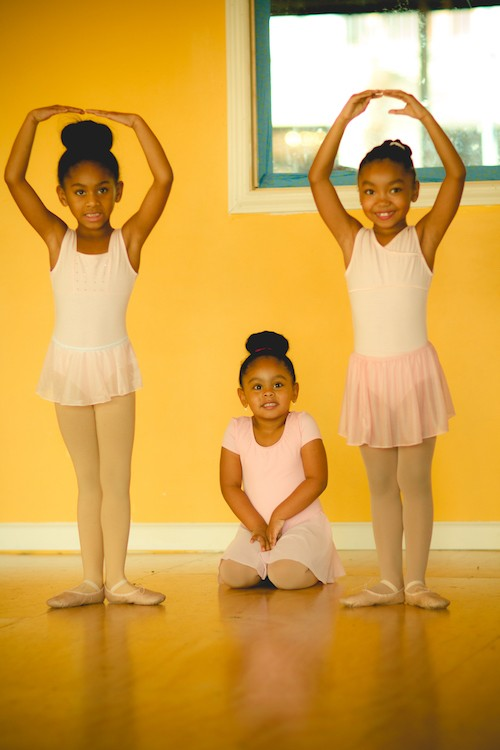 Three young ballet students in white leotards and skirts. Two girls stand in first position with their arms above their head.
