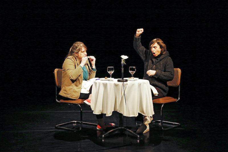 Andrea Kleine sits at a table with a fellow performer. There are empty wine glasses on the table and they eat quail.