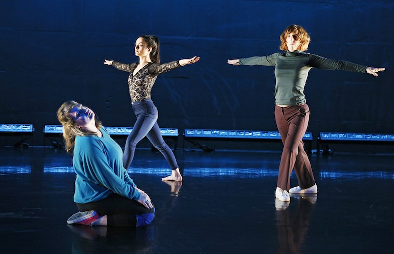 Two performers in pants and long sleeve shirts stand in a lunge with their arms stretching out at their sides. A third performer sits on her shins and her head extends back.