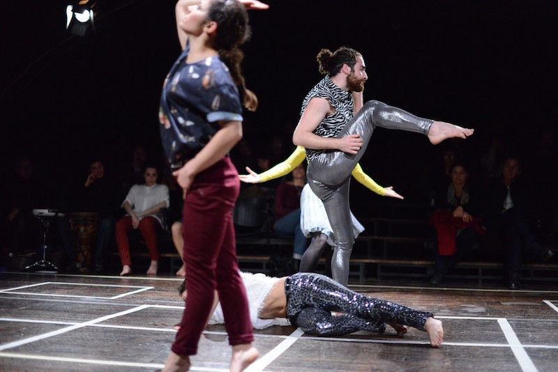 Dancers perform a grided stage and wear shiny pants