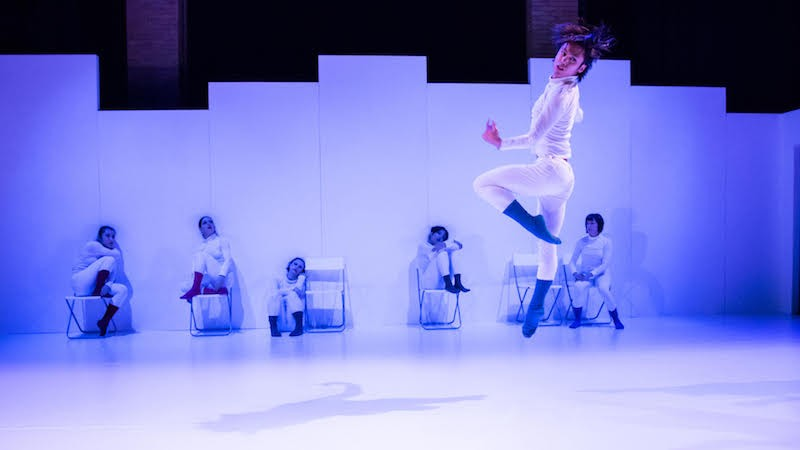 Dancers dressed in white save for colorful socks sit against a wall while another jumps into the air looking over their shoulder