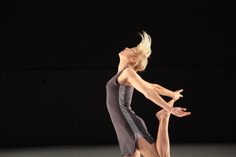 Liz Gerring in a racer back athletic-looking tunic kicks her leg behind her. Her head looks to the ceiling as her short blonde hair tosses up.