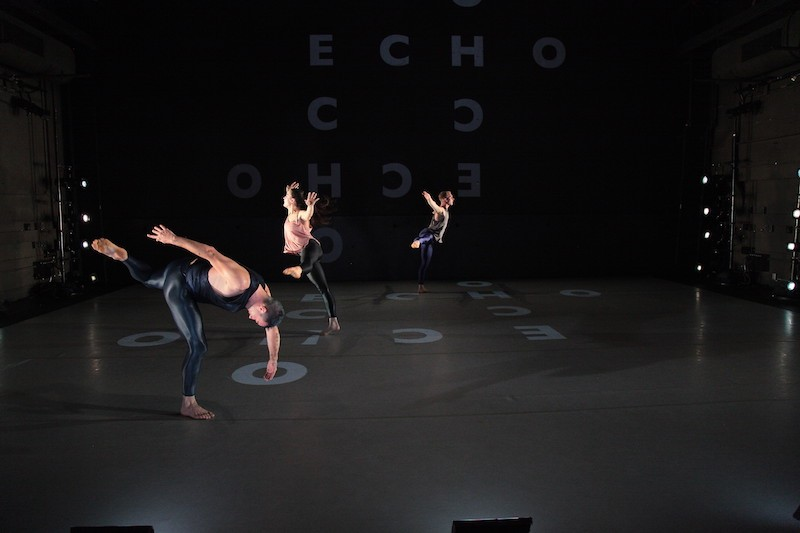 Three dancers in shiny black leggings and tank tops stand on letters that are projected on the floor in off-kilter balances and stances.