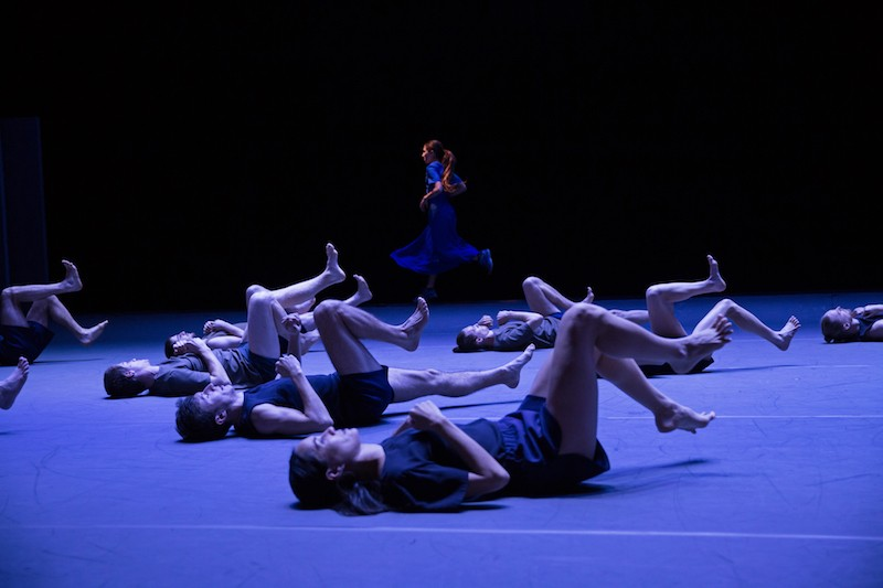 A woman in a blue dress runs in the background as a group of dancers in black costumes lay on the floor with their legs in the air