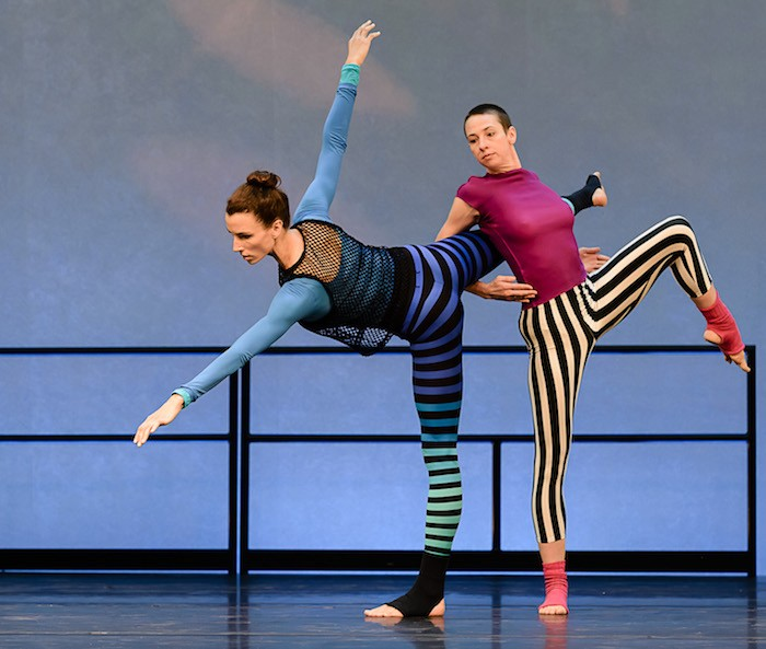 Two female dancers in bold striped leggings. One executes a penchee arabesque while the other hooks her arms around her counterpart's raised back leg. She too balances on one leg.