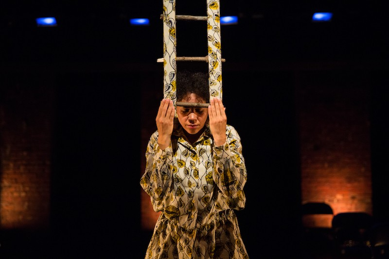 A woman in a yellow printed blouse presses a small prop resembling a mini ladder in front of her. Her head is bowed. The prop is the same pattern as her blouse.