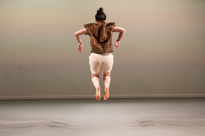 Lily Bo Shapiro jumps in the air with her feet and legs tucked underneath her. Her elbows make an almost ninety degree angle. Her back is towards the audience