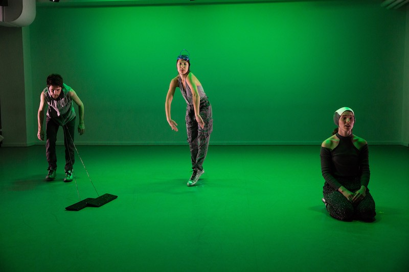 The space is cast in green as three dancers mingle in the space. One has two strings attached to his neck that are connected to computer keyboards
