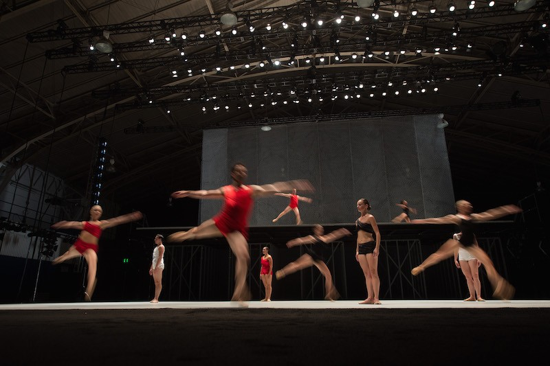 Several dancers in red jump in arabesque while others stand still