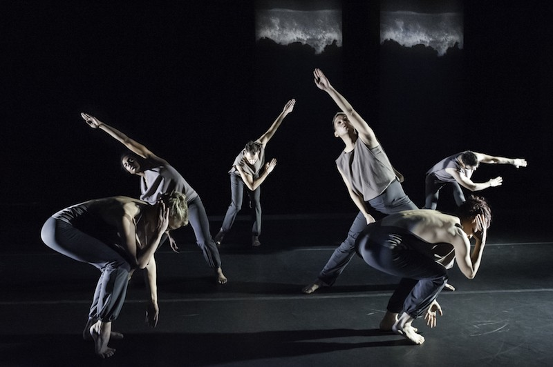 Six dancers arranged in a symmetrical configuration. Two dancers bend their torsos to rest on their thighs. Two dancers reach their arm that is center overhead on a diagonal. Two additional dancers upstage swing their arms to their sides.