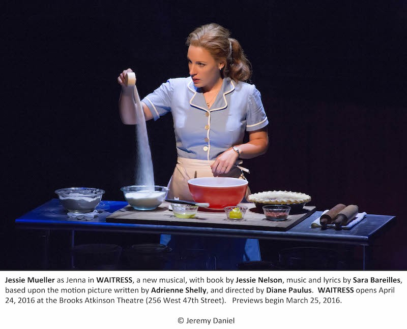 Jenna Mueller from the Waitress stands behind a table with pie ingredients.