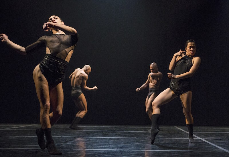 Dancers in black briefs and leotards sway the hips and gesticulate. Two men in the background stand with legs together.