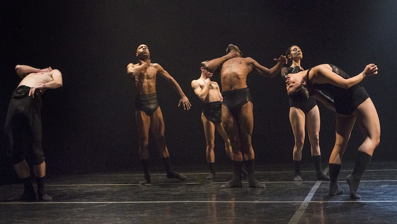 Dancers wearing black briefs stumble behind themselves with their hands around their necks. Two dancers perform deep back bends.