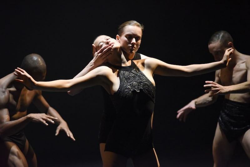 A dancer in a black lace leotard outstretches her arms. Behind her is another dancer whose hand is over the outstretched artist's mouth.