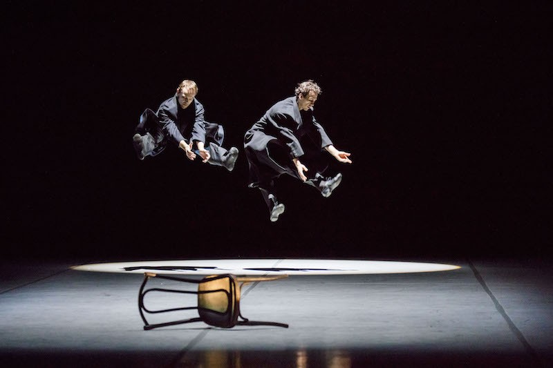 Two men jump with their legs outstretched into the air. Chairs lay on the ground.