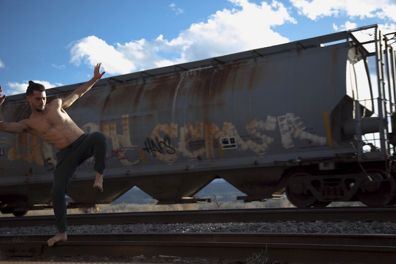 A man, shirtless and barefoot, balances on train tracks. An old train is behind him.