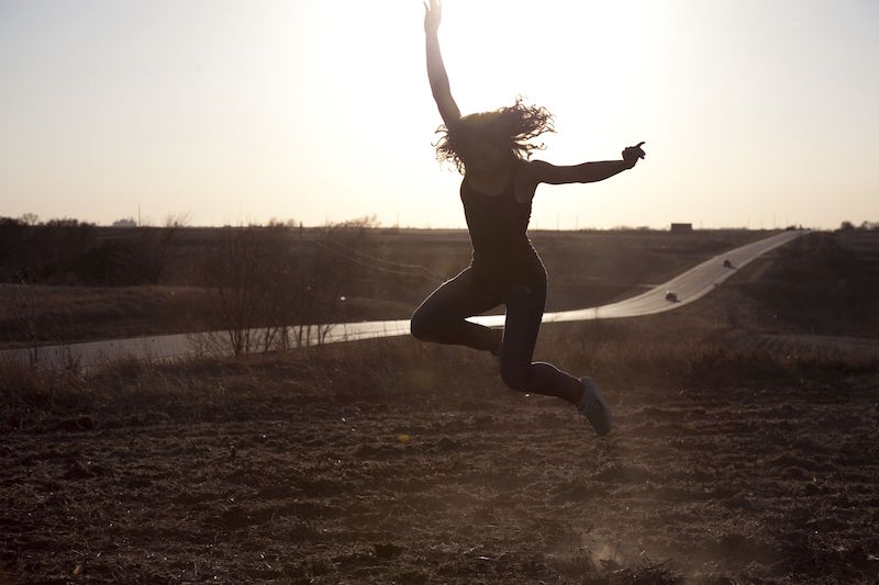 A woman in a field on the side of a highway leaps into the air as the sun sets
