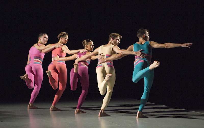 A quintet in sherbet colored unitards link arms with the backs to the audience. They balance on leg and look over their shoulder.