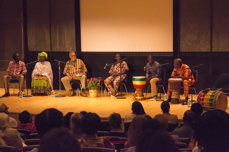 Panelists sit in a line facing the audience in chairs dressed in colorful garb