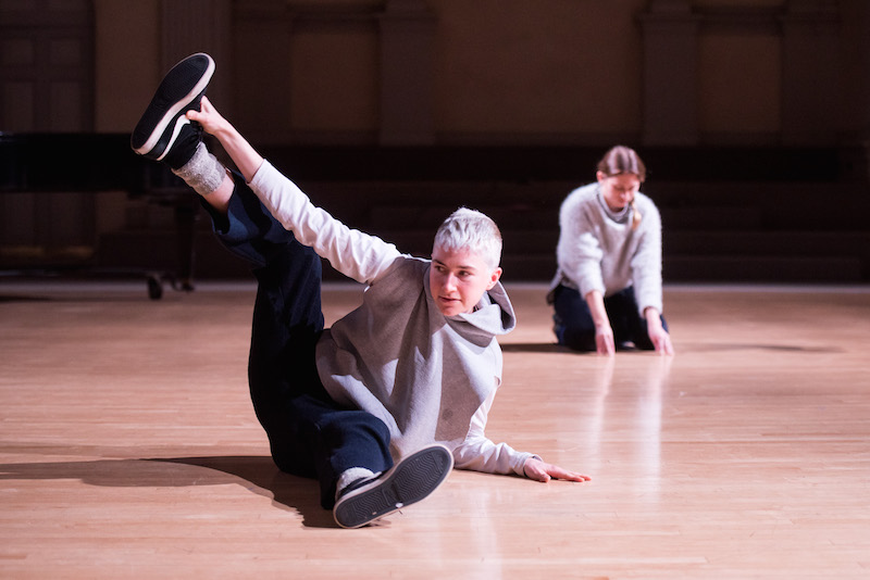 Two women sit on the floor in grey sweatshirts, blue pants and sneakers. The person in the foreground tips her hip to one side and holds on to her foot in the air