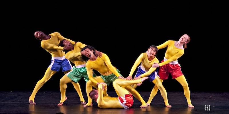 Members of Pilobolus in gold body suits and gym shorts pulling at one another's faces to create a humorous tableau.