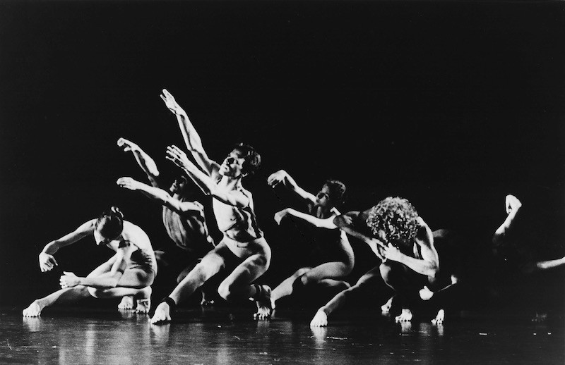 A group of dancers crouching on the ground in Posin's original performance of Waves in 1973