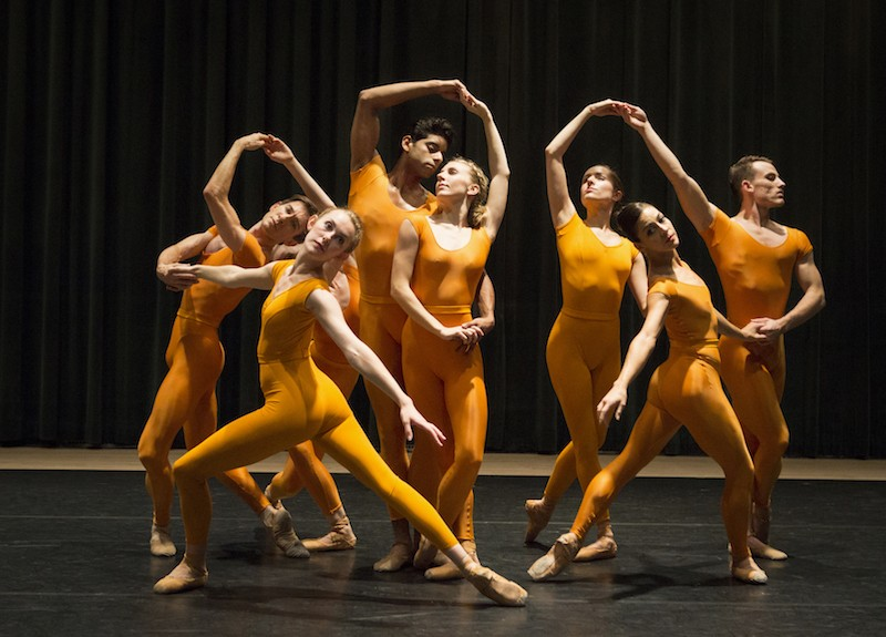 A group of dancers link hands to form a human chain in marigold unitards