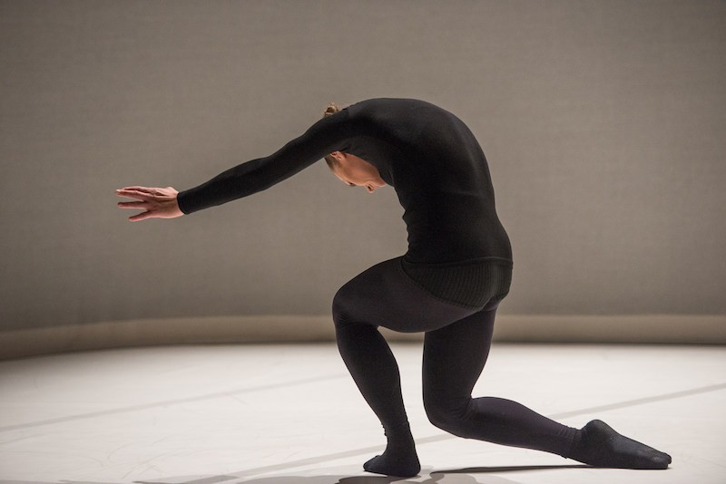 A dancer in all black curves her back over and her arms are outstreched