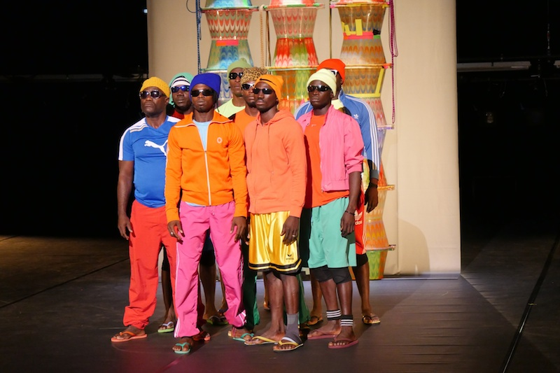 A group of black men looking out in sunglasses and bright colored athletic apparel