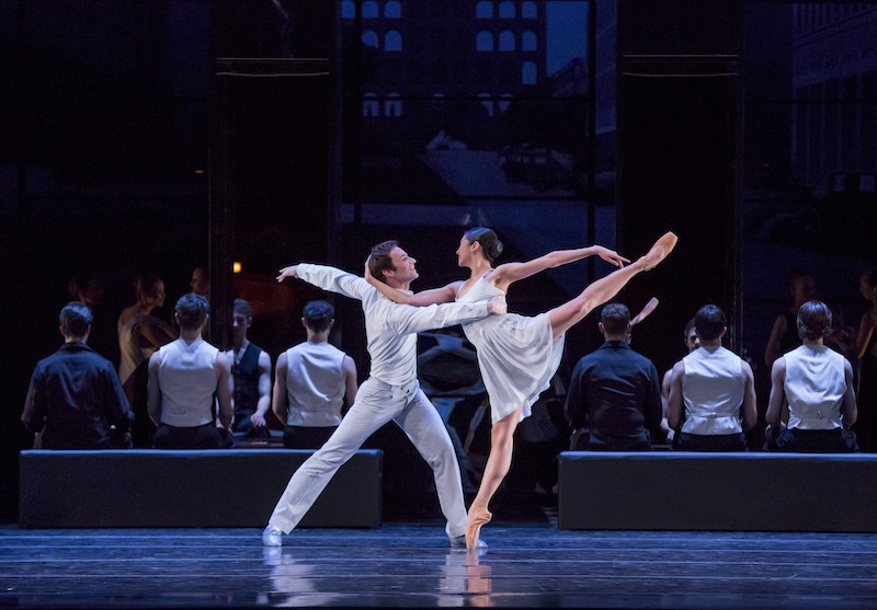 A woman on pointe in arabesque. Her arm hooks around her partners head and he steadies her by holding her rib cage.