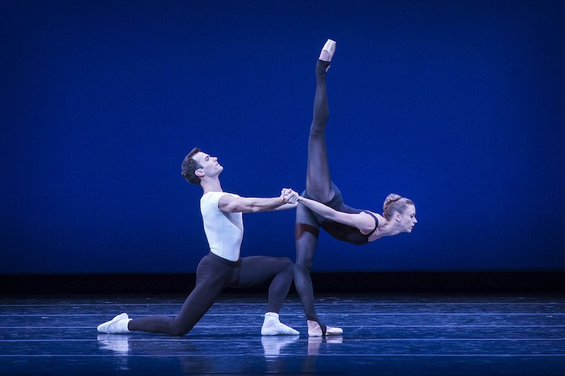 The male dancer is on one knee as he clasps his hands on his partner's. She extends her leg in an arabesque penchee