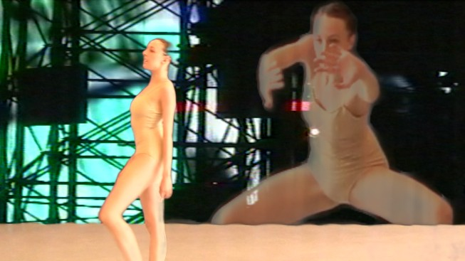 Dancer Dona Wiley in a nude leotard bevels her foot looking straight ahead. There is a projected image of her in a crouch behind her.