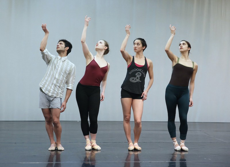 Four dancers stand in a horizontal line. Their right arm gestures above their head as if they're holding a chalice from its stem.