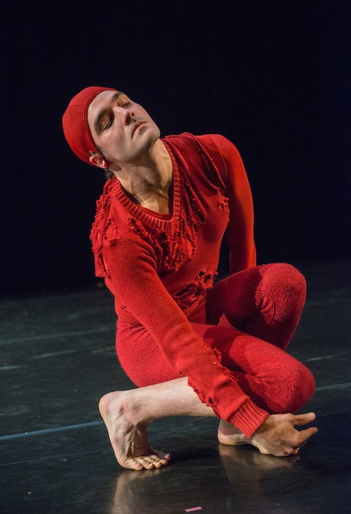 Silas Riener in a red knitted cap, tattered sweater and knit pants crouches near the ground