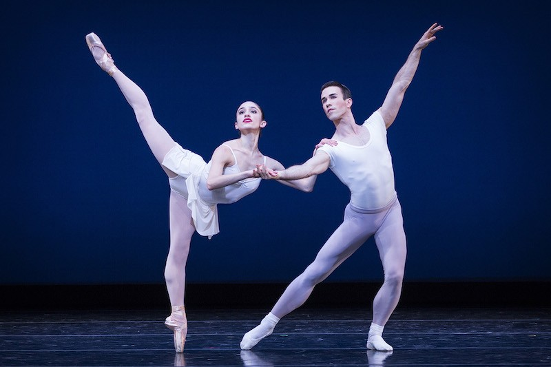 A woman en pointe leans on her male partner, who is in a lunge, and raises her leg high behind her in an arabesque