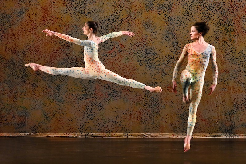 Two women in unitards with tiny colorful dots jump in front of a back drop with same dot pattern which is reminiscent of pointillism