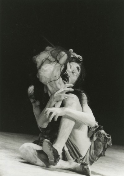 Master Butoh Dancer Tatsumi Hijikata in a contorted sitting position while a grotesque mask rests on his face